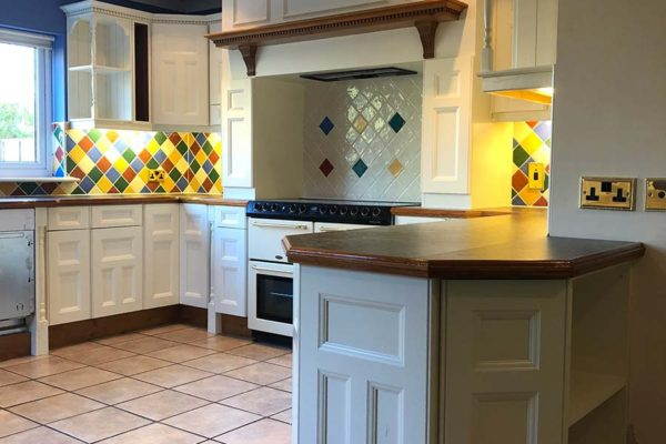 white sprayed kitchen cupboards with eyecatching tiles