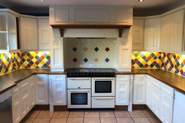 white kitchen showcasing oven with vibrant tiles
