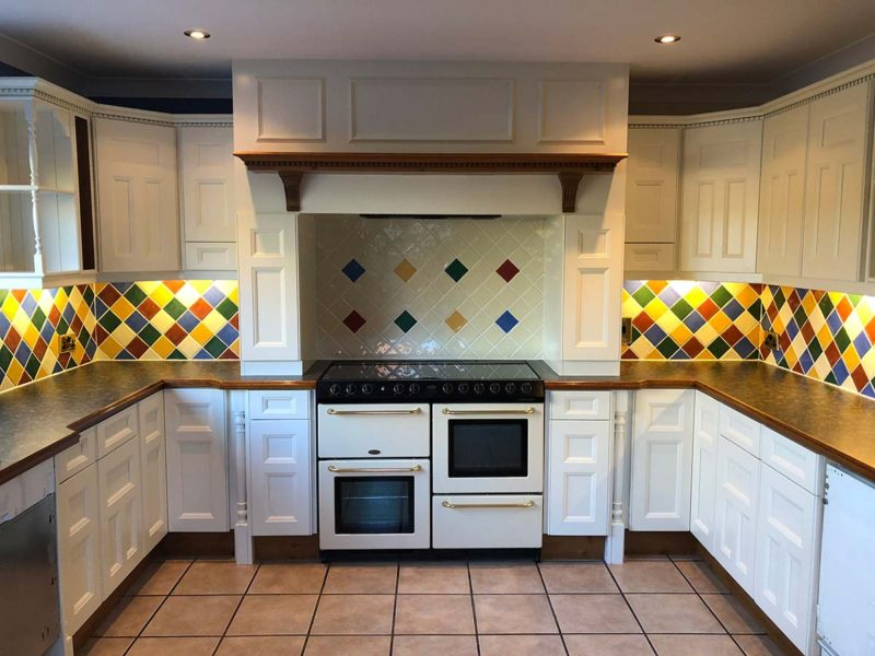 white kitchen showcasing oven with vibrant tiles