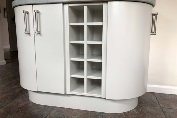 White kitchen island with wine shelves